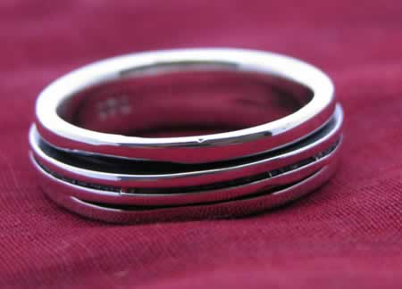 Sterling silver band with two thin strips wrapping another band that spins around.